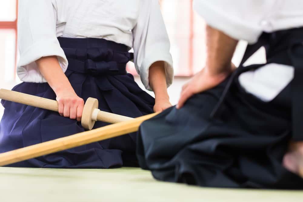 Man and woman fighting with wooden swords at Aikido