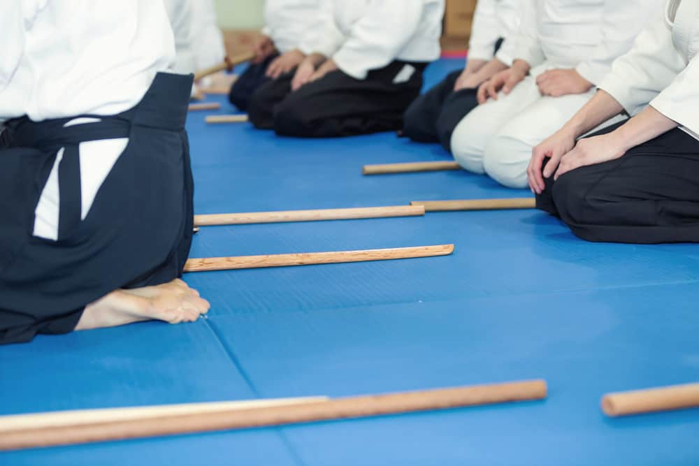 People in kimono on martial arts weapon training Aikido
