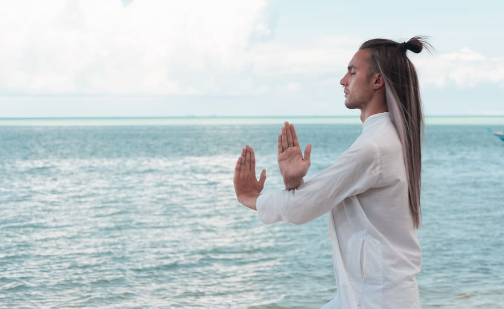 man with long hair is practicing Taijiquan on the beach