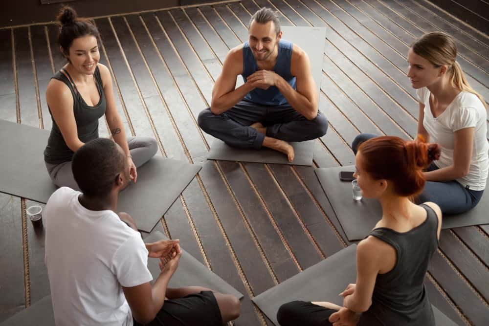 people sitting on mats in circle relaxing talking before yoga