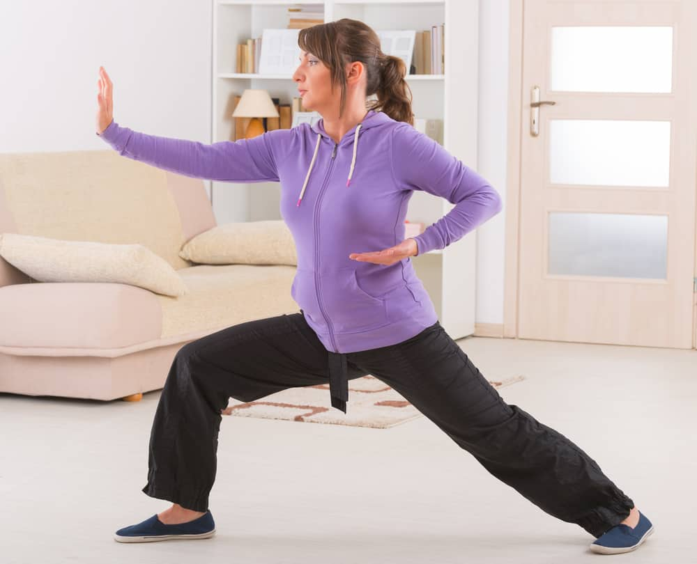 woman doing qi gong tai chi exercise at home